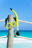 Yellow snorkeling mask hanging on the wooden stake Stock Photography