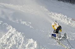 Yellow snow maker machine snow gun, snow cannon at ski slopes resort - standard equipment device for making snow to create bette Stock Images
