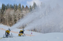 Yellow snow maker machine snow gun, snow cannon at ski slopes resort - standard equipment device for making snow to create bette Royalty Free Stock Images