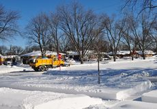 Yellow snow plow truck clearing snow in residential area. Royalty Free Stock Photo