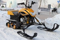 Yellow snowmobile stands near the ice town on the street of the Royalty Free Stock Photography
