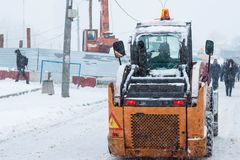 Yellow snowplow removing snow. During heavy snowfall. Winter street maintenance in hard weather conditions Stock Photos