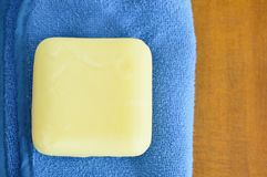 Yellow soap and blue towel on wooden table Royalty Free Stock Images
