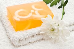 Yellow soap on towel. Handmade soap and white flower on towel royalty free stock images