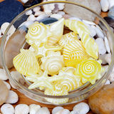Yellow soaps with shapes of shells and starfish and many little Royalty Free Stock Photography