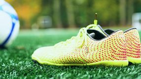 Soccer ball and football boots on green grass. Yellow soccer ball and football boots on green grass stock photo