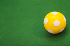 Yellow Soccer ball on green field Stock Photography