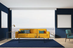 Yellow sofa, blue living room. Blue living room interior with a yellow sofa, gray, blue and black pillows, a blue carpet, two framed square posters and loft Royalty Free Stock Images