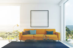 Yellow sofa, blue pillows living room toned. White living room interior with a yellow sofa, gray, blue and black pillows, a blue carpet, a framed square poster Stock Photo
