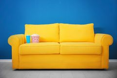 Yellow sofa with popcorn and drink in home cinema. Watching movie royalty free stock photos