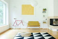 Sofa between bicycle and shelf. Yellow sofa between red bicycle and white shelf in cosy living room with fireplace and pouf on carpet Royalty Free Stock Image
