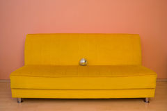 Yellow sofa with small discoball Stock Photos