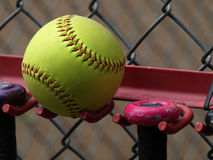 Yellow Softball. A yellow softball resting on a bat rack against a chain link fence at a playing field. Exterior shot Stock Images