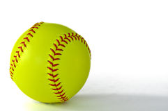 Yellow Softball. With red stiching  on white Royalty Free Stock Photography