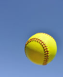 Yellow Softball in the Air. Against a Blue Sky Royalty Free Stock Photos
