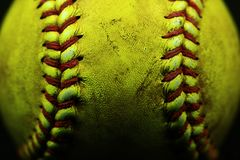 Yellow softball closeup with red seams on black background.