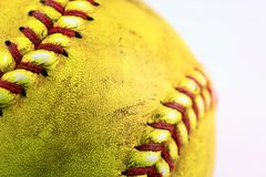 Yellow softball closeup with red seams on white background. Closeup of yellow softball with many red seams on white background royalty free stock photo