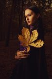 Yellow sorrow. Portrait of pretty gothic girl with leaves Royalty Free Stock Photography