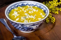 Yellow soup with blue cheese topping Stock Images