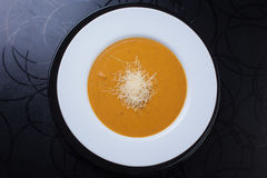 Yellow soup with grated cheese stock images