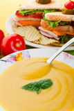Yellow soup and sandwich. Yellow soup with tomato and sandwich focus on the soup Royalty Free Stock Photos