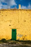 Yellow spanish house with green door Stock Images