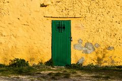 Yellow spanish house with green door Stock Photo