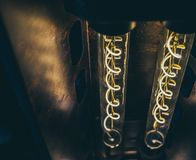 Yellow spiral light in glass tubes glowing in the dark. Retro style ceiling lamps with copy space royalty free stock photos