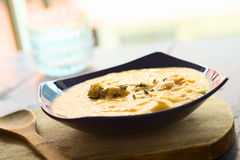 Yellow Split Pea Soup. Thick yellow split pea soup with chicken and some oregano leaves on top served in blue soup plate on wooden board (Selective Focus, Focus royalty free stock images