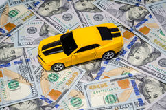 Yellow sport car on american dollars money background. Yellow sport car on american dollars bills paper money background Royalty Free Stock Images