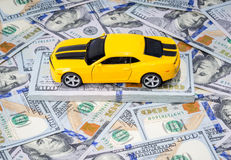 Yellow sport car on american dollars money background. Yellow sport car on american dollars bills paper money background Royalty Free Stock Photo
