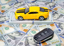 Yellow sport car with keys on money background. Yellow sport car with keys on american dollars bills paper money background Stock Image