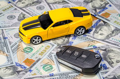 Yellow sport car with keys on money background. Yellow sport car with keys on american dollars bills paper money background Royalty Free Stock Image