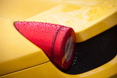 Yellow sport car tail light with rain drops royalty free stock image