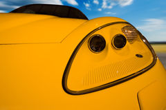 Yellow sports car. Driving fast - blue sky on the background is blurred Royalty Free Stock Photos