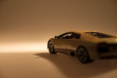 Yellow sports car illuminated. With dark background Royalty Free Stock Photography