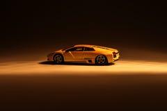 Yellow sports car illuminated. With dark background Royalty Free Stock Photos
