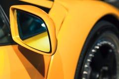 Yellow sports car mirror, close up photo. Italian car design Stock Photography