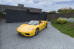 Yellow sports car. Modern design yellow sports car parked outside a contemporary house Stock Image