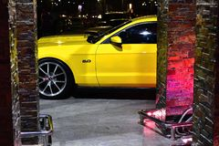 Yellow sports cat behind decorative walls with lights in color. FaST CARS ARE sport in nature and so expensive they are for rich and famous people as well as Royalty Free Stock Photos