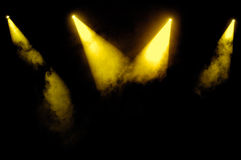 Yellow Spotlights. Yellow stage spotlights in smoke over black background royalty free stock photos