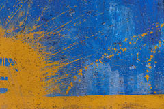 Yellow spray on blue painted wall Royalty Free Stock Images