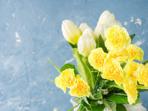 Yellow spring Easter pastel color flowers on blue. Copy space Stock Photos