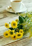 Yellow spring flowers and cup of tea on old wooden Stock Photo