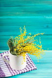 Yellow spring flowers of mimosa in a white mug on a blue wooden background. Royalty Free Stock Image