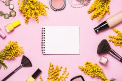 Yellow spring flowers, notebok and some cosmetics on pink spring background stock image