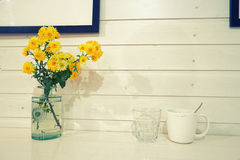 Yellow spring flowers in vintage glass bottles and Royalty Free Stock Images