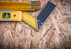 Yellow square ruler construction level wooden meter on chipboard Royalty Free Stock Photos