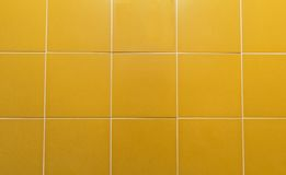 Yellow squared wall. A wall with squared tiles of yellow mustard color Stock Photography