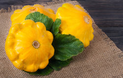 Yellow squash on a wooden background with napkin of burlap Stock Image